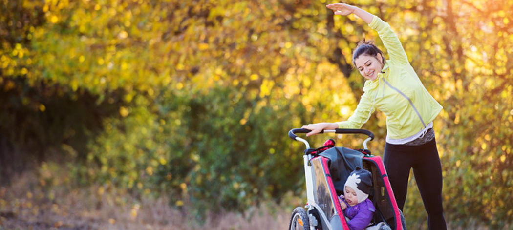 Background image of athletic woman standing by stroller stretching